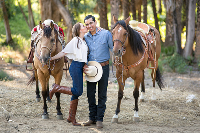 Kissing him at Fairmount Park, Engagement Photo with Horses by Temecula Wedding Photographer