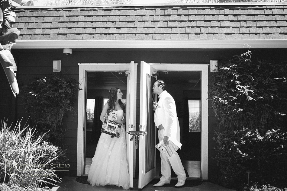 bride and groom kissing each other behind the door by temecula wedding photographer