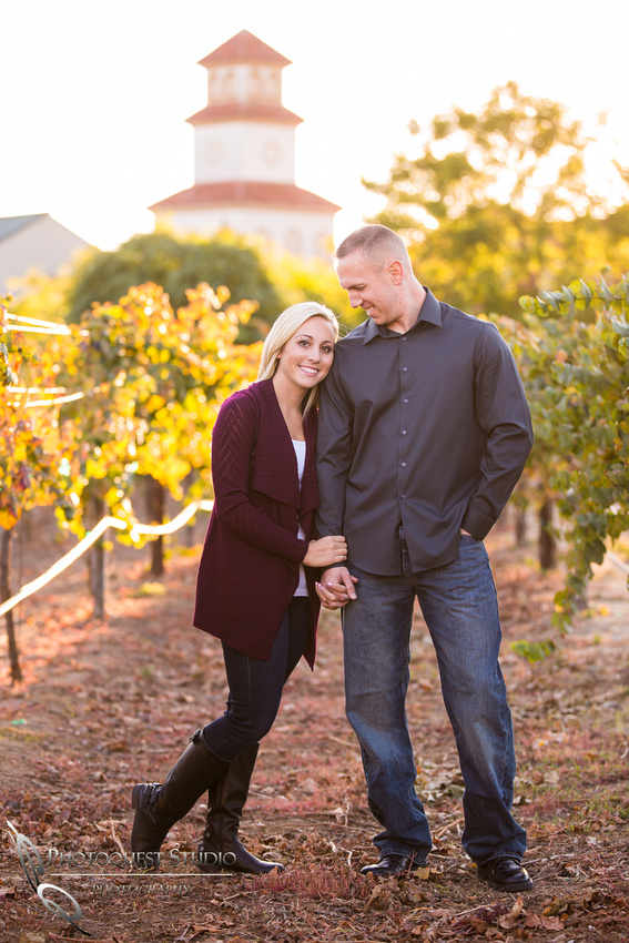 Looking at her in vineyard at Engagement photo at South Coast Winery, California by Temecula Wedding Photographers