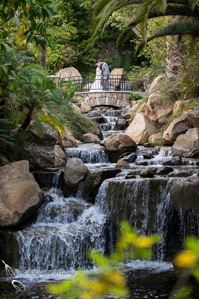 Kissing by the waterfall. Wedding photos at Grand Tradition Estate Fallbrook by Wedding Photographer in Temecula