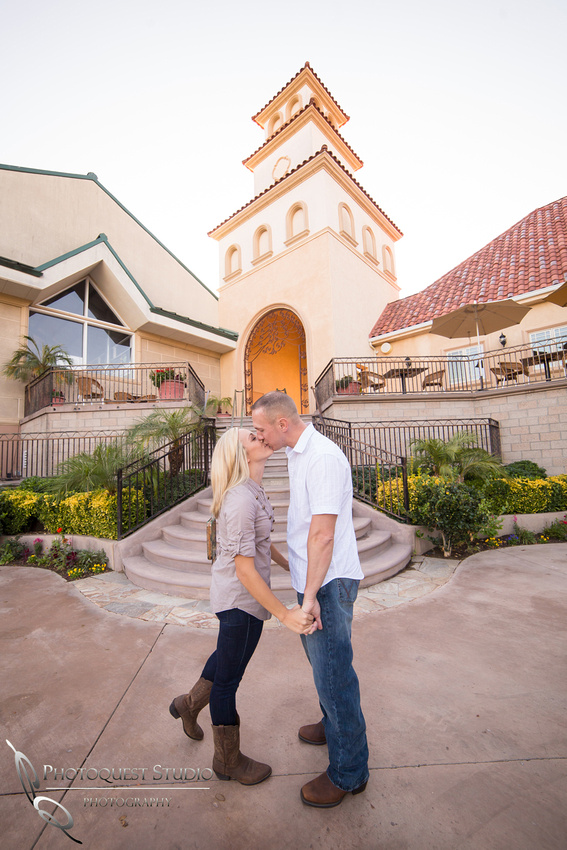 Couple kissing by the clock tower at Engagement photo at South Coast Winery, California by Temecula Wedding Photographers