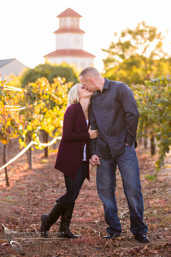 Kissing in front of the vineyard at Engagement photo at South Coast Winery, California by Temecula Wedding Photographers
